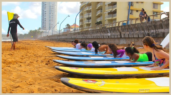 Girls laying on surfboards during surfing in Puerto Rico beginner surfing lessons